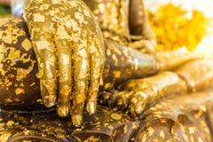 Ponga la hoja de oro sobre la estatua de Buda para dorar Qué gente utiliza t Fotos de archivo