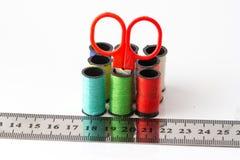 Ponga las tijeras en los hilos de coser y regla multicolores en el fondo blanco Imagen de archivo libre de regalías