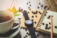 Ponga letras a los granos de café de la historia por la mañana en el fondo de madera Foto de archivo