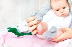 Ponga los calcetines grises en el bebé recién nacido Fotografía de archivo libre de regalías