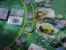 Ponga para jugar la veintiuna en el casino Vidrios del whisky y de Martini en la tabla foto de archivo libre de regalías