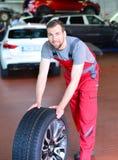 Ponga un neumático el cambio en el coche en un taller de un mecánico imagen de archivo libre de regalías