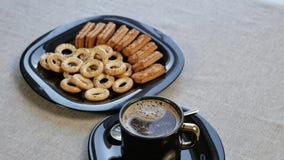 Ponga una taza de café en la tabla Hay una placa con las galletas hechas en casa en la tabla almacen de video
