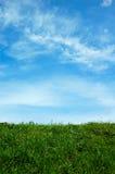 Ponga verde el campo y un cielo azul Imagen de archivo