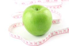 Ponga verde la manzana y la cinta de medición Foto de archivo libre de regalías