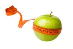 Ponga verde la manzana y la cinta de medición Imagenes de archivo