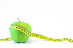 Ponga verde la manzana y la cinta de medición Fotos de archivo