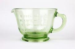 Ponga verde la taza de medición de cristal de la depresión Imágenes de archivo libres de regalías
