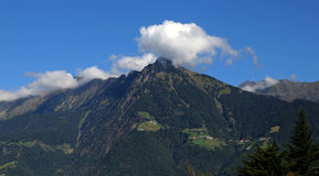 Ponga verde las montañas con las nubes y el cielo azul Fotos de archivo