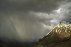 Ponga verde los rayos antes de la puesta del sol en montañas Imagenes de archivo