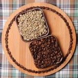 Ponga verde y asó los granos de café en dos cuencos cuadrados en el tablero de madera con el circuito de los granos de café En fo Imagenes de archivo