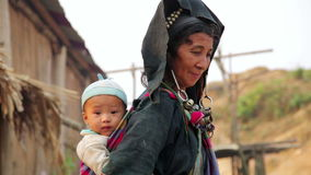 PONGSALI, LAOS - APRIL 2014: native Akha woman carry baby stock footage