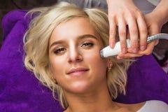 Poniendo a la mujer que consigue el laser y el ultrasonido terapia facial en balneario Foto de archivo
