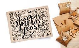Poniendo letras a la tarjeta de felicitación de la Feliz Año Nuevo - mande un SMS en el documento de Kraft del vintage sobre un f Fotos de archivo libres de regalías