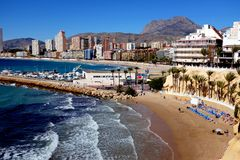 Poniente beach, Benidorm, Spain. Benidorm, Spain.  March 07, 2018.  Holidaymakers enjoy the small beach of Mal Pas and walk along the prpmenade of Poniente Stock Image