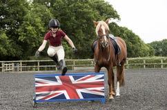 Ponnyryttare som hoppar ett lågt staket Royaltyfria Bilder