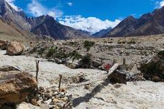 Pont accrochant au-dessus de la rivière sauvage sur le chemin au camp K2 de base photo stock