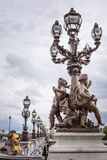 Pont Alexandre III bridge. With cherubs statue and row of lanterns Royalty Free Stock Images