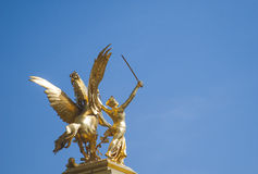 Pont Alexandre III Bridge Golden Statue Paris France. A golden statue of a winged horse spreading its wings and a naked woman with a sword at the Pont Alexandre Royalty Free Stock Photos