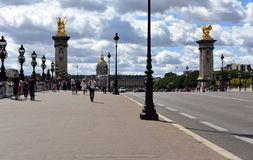 Paris, France. Alexandre III Bridge and Invalides with tourists. Columns, statues and street lights, rainy day. royalty free stock photography