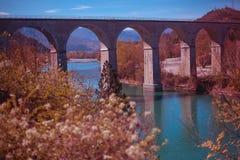 Pont arqué français sur une rivière avec des arbres de floraison dans le premier plan images libres de droits