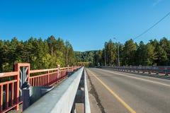 Pont au-dessus d'une rivière Katun de montagne photos stock