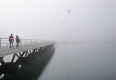 Pont au-dessus de l'eau avec des personnes dans le brouillard Photo libre de droits