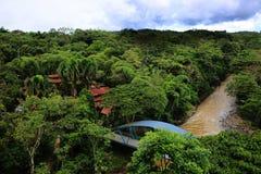 Pont au-dessus de la rivière brune menant aux maisons dans le middel de la jungle photo stock