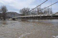 Pont au-dessus de la rivière en crue Images stock