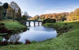 Pont au-dessus de lac principal dans des jardins de Stourhead pendant l'automne Photographie stock