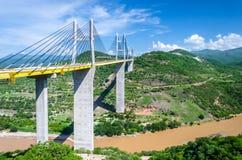 Pont au-dessus de rivière avec les montagnes vertes dans le jour coloré ensoleillé Image stock