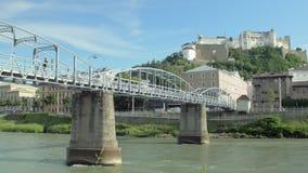 Pont au-dessus de rivière de Salzach de vue et vue sur la forteresse de Hohensalzburg à Salzbourg banque de vidéos
