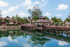 Pont avec des fleurs à travers la baie dans un jardin tropical Images libres de droits