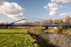Pont bleu en route avec la rivière, l'herbe et le ciel bleu avec des nuages dans la ville de Karvina dans la République Tchèque images libres de droits