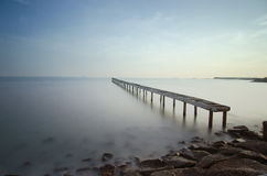 Pont cassé et vagues se brisant sur la mer à pendant le coucher du soleil Image stock