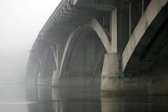 Pont concret de voûte au-dessus de la rivière dans le brouillard Photographie stock