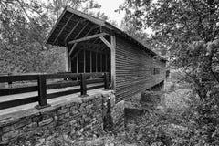 Pont couvert au-dessus de crique de montagne en noir et blanc Images libres de droits
