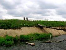 Pont délabré de pied au-dessus de l'eau boueuse Photographie stock