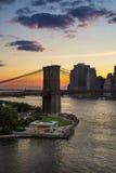 Pont de Brooklyn, carrousel et secteur financier au coucher du soleil, New York City Photos stock