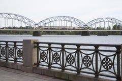 Pont de chemin de fer avec le train et les banques de la dvina occidentale de rivière, Riga Photographie stock