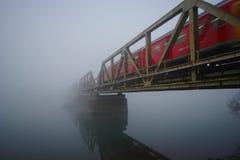 Pont de chemin de fer avec le train rouge dans le brouillard Photos stock