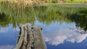 Pont de CkgroundA de vieux faisceaux au-dessus de la rivière, d'une réflexion du ciel bleu et des nuages image stock