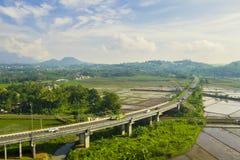 Pont de manière de péage de Transport-Java avec des terres cultivables image libre de droits