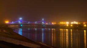 Pont de Starovolzhsky dans le brouillard et l'éclairage de nuit Image stock