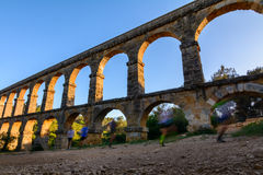 Красивый вид римского Мост-водовода Pont del Diable в Таррагоне на заходе солнца при люди jogging перед им Стоковая Фотография