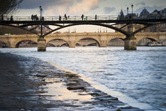 Pont des Arts in Paris, France. Pont des Arts and river Seine in Paris, France. Pont Neuf in the background. Silhouettes of tourists and people on the bridges Stock Photography