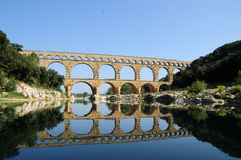 Pont du Gard. Roman aqueduct running over the Gardon river valley with blue skies and dramatic reflection in still water Stock Photography