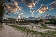Pont du Gard bij zonsondergang met stralen van de zon stock afbeelding