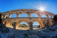 Pont du Gard contra puesta del sol es un acueducto romano viejo en Provence, Francia Foto de archivo libre de regalías