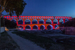 Pont du Gard Provence. The Pont du Gard roman bridge with arches in Provence, France red lighten at night Stock Photos